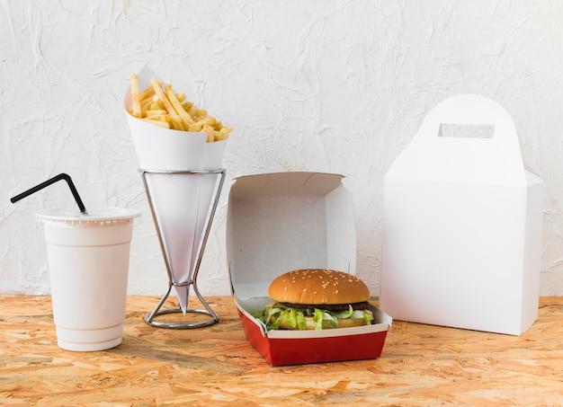 Fast food com copo de eliminação e pacote de comida simulado na mesa de madeira Foto gratuita