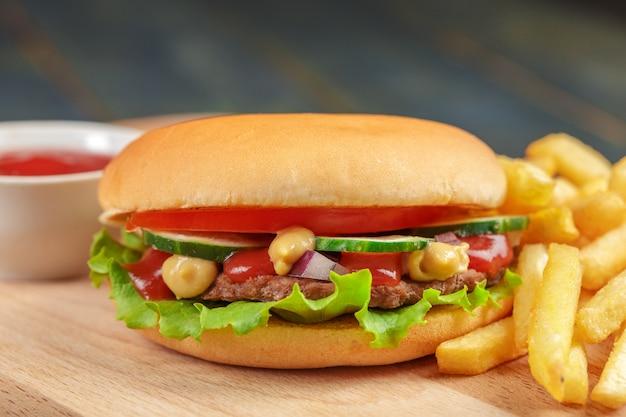 Fast food, hambúrguer caseiro em um fundo de madeira Foto Premium