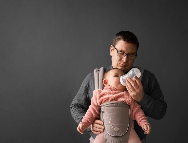 Fathre e seu filho no porta-bebê na parede de fundo cinza, bebê vestindo em paternidade Foto Premium