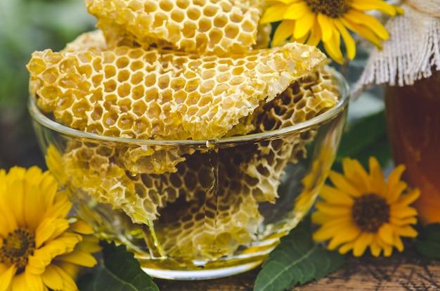 Fatia amarela do favo de mel. fatia de célula de mel. tigela com favos de mel e mel Foto Premium