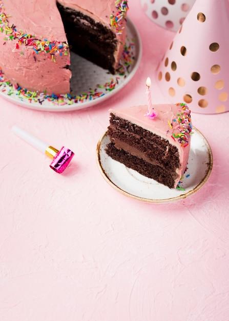 Fatia de alto ângulo de bolo rosa com vela Foto gratuita