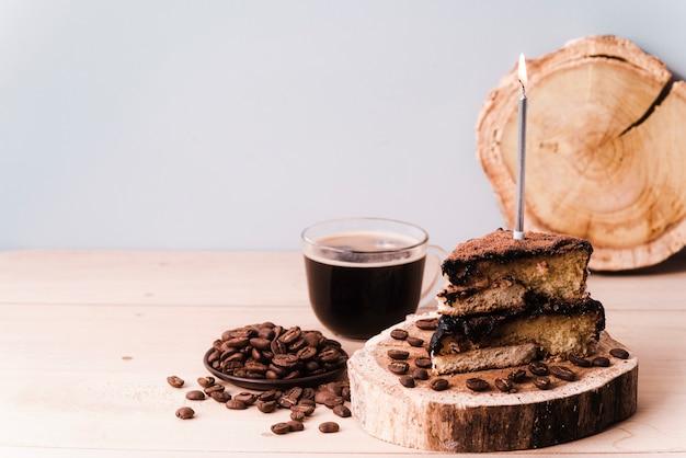 Fatia de bolo com vela e grãos de café e copie o espaço Foto gratuita