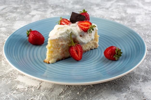 Fatia de bolo delicioso vista frontal perto dentro da placa azul com creme e morangos Foto gratuita