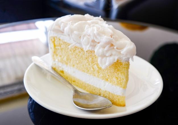 Fatia de bolo fatia de bolo de baunilha creme na chapa branca sobremesa de leite de bolo de coco na cafeteria Foto Premium