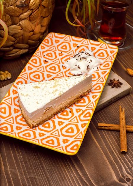 Fatia de cheesecake de baunilha caramelo no prato contra uma mesa de madeira marrom rústica Foto gratuita