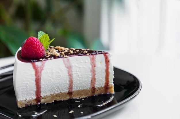 Fatia de cheesecake de framboesa saborosa com molho de cerâmica preta Foto gratuita