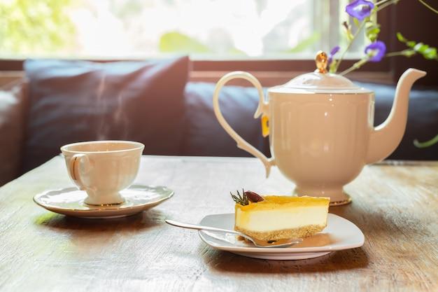 Fatia de cheesecake de limão com uma xícara de chá com flores. Foto Premium