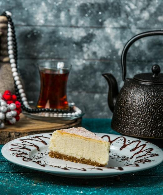Fatia de cheesecake em chapa branca, servida com chá preto Foto gratuita