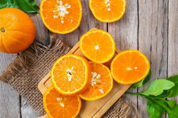 Fatia de fruta fresca de laranjas em um de madeira Foto Premium