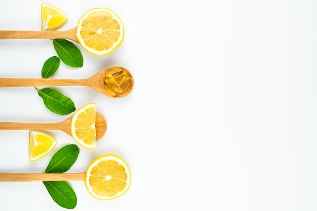 Fatia de limão e vitamina c cápsula em suplementos de colher de pau para uma boa saúde, fundo branco, conceito de medicina e drogas Foto Premium