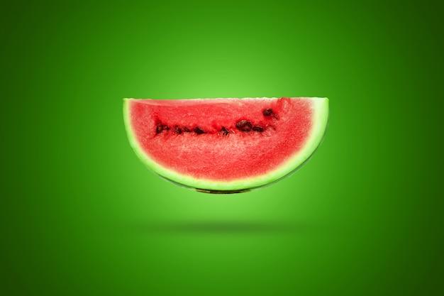 Fatia de melancia sobre um fundo verde Foto Premium
