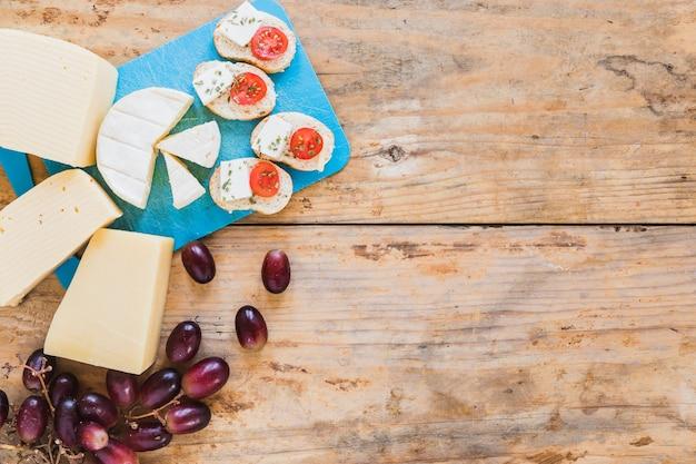 Fatia de pão com tomate e queijo com uvas na mesa Foto gratuita