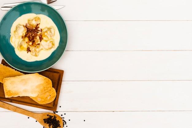 Fatia de pão e massa cremosa de ravióli com molho branco na superfície de madeira Foto gratuita