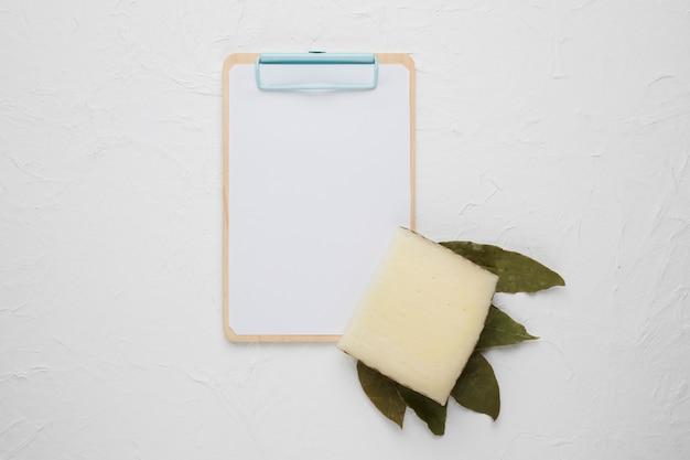 Fatia de queijo; folhas de louro secas e prancheta no pano de fundo branco Foto gratuita