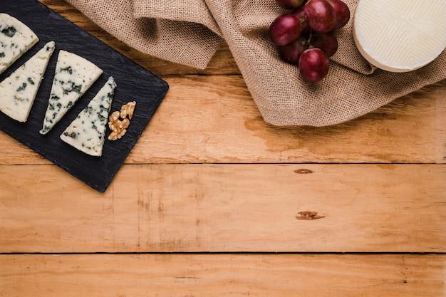 Fatia de queijo gorgonzola; noz em pedra preta com uvas e queijo manchego espanhol sobre textura de serapilheira Foto gratuita