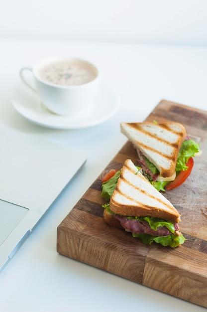 Fatia de sanduíches de presunto e xícara de café no fundo Foto gratuita
