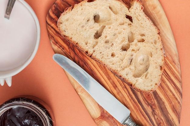 Fatia do pão e faca de manteiga na placa de desbastamento com leite e doce no fundo colorido Foto gratuita