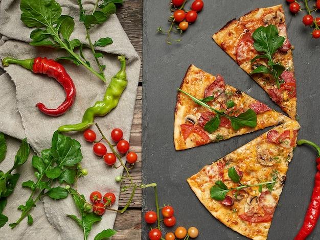 Fatia triangular de pizza assada com cogumelos, linguiças defumadas, tomate e queijo Foto Premium
