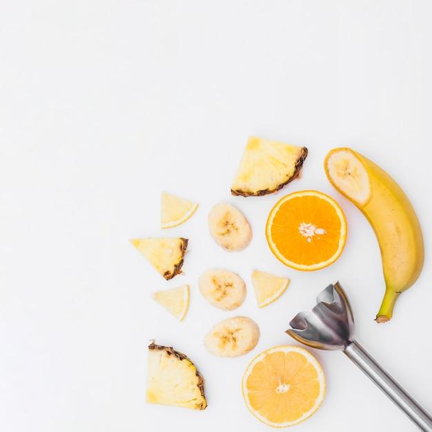 Fatias de banana; abacaxi; laranjas cortadas ao meio com o misturador da mão no fundo branco Foto gratuita