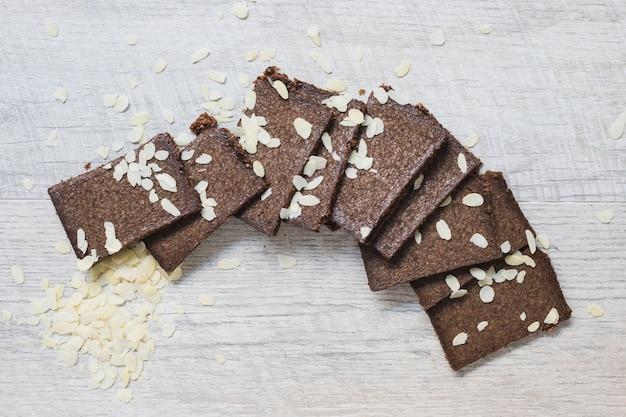 Fatias de barras de chocolate e amêndoas em pano de fundo texturizado branco de madeira Foto gratuita