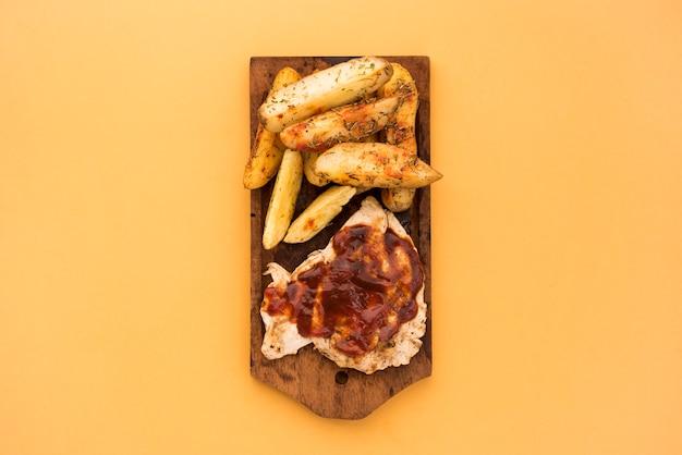 Fatias de batata e carne com molho na placa de madeira Foto gratuita