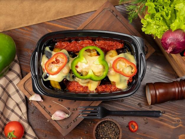 Fatias de berinjela grelhadas recheadas com carne e queijo derretido no topo com fatias de pimentão takeaway Foto gratuita