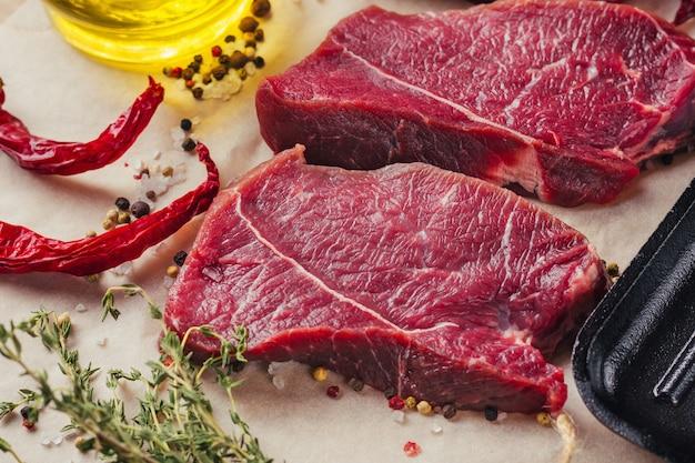 Fatias de bife de carne crua fresca com especiarias e azeite pronto para cozinhar Foto Premium