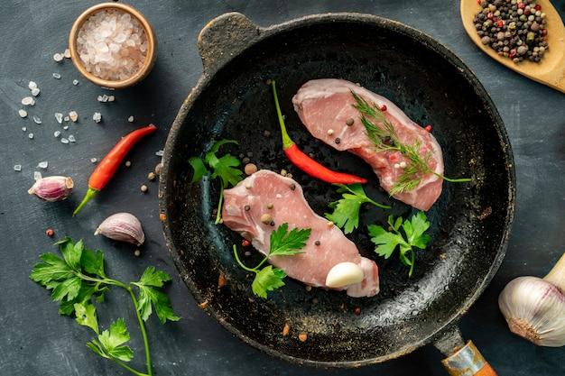 Fatias de carne de porco crua ou bifes em uma frigideira quente na cozinha, estilo de foto rústica witj ingrediente Foto Premium