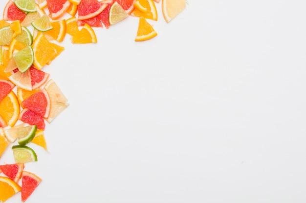 Fatias de frutas cítricas coloridas no canto do fundo branco Foto gratuita