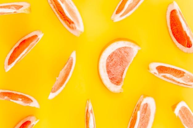 Fatias de frutas cítricas em fundo amarelo Foto Premium