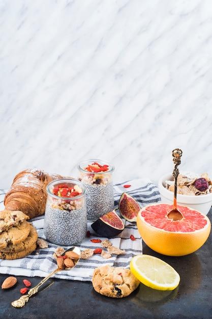 Fatias de frutas cítricas; smoothie saudável com biscoitos e croissant no guardanapo Foto gratuita