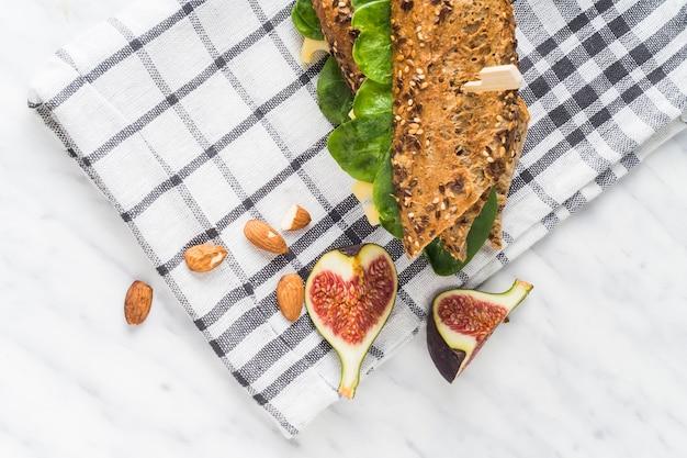 Fatias de frutas frescas de figo e amêndoas perto de cachorro-quente sobre guardanapo no balcão da cozinha Foto gratuita