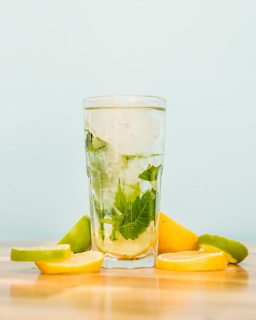 Fatias de frutas perto de copo de bebida com gelo e ervas Foto gratuita
