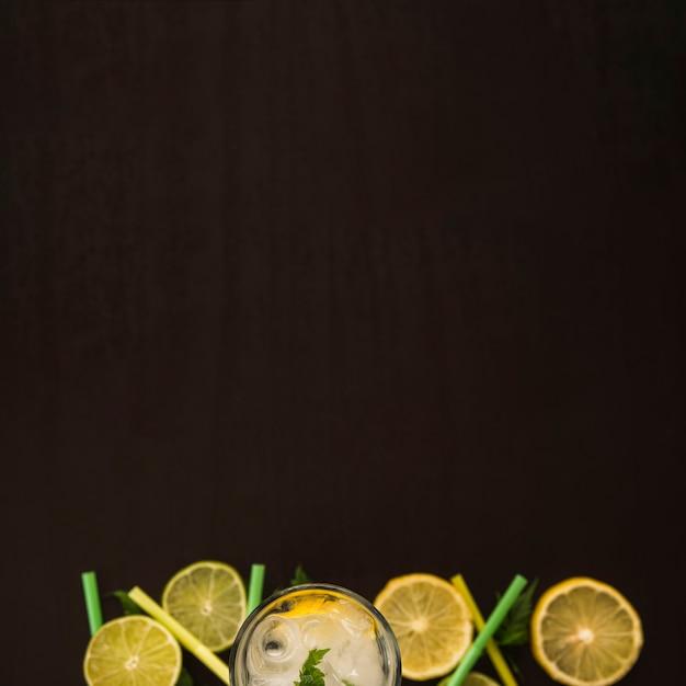Fatias de frutas perto de vidro com gelo Foto gratuita