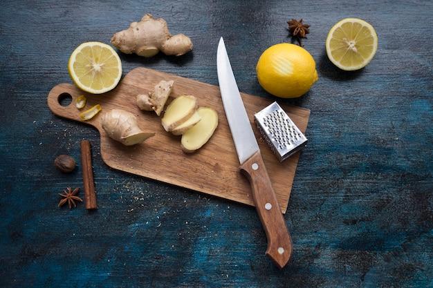 Fatias de gengibre na placa de madeira com limão Foto gratuita
