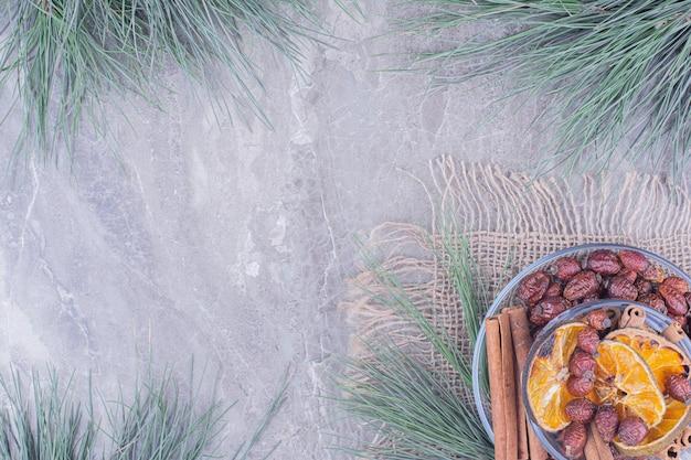 Fatias de laranja secas e quadris com canela em um copo de vidro Foto gratuita