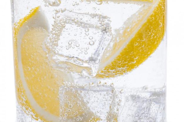 Fatias de limão amarelo suculento fresco com gelo na água clara. Foto Premium