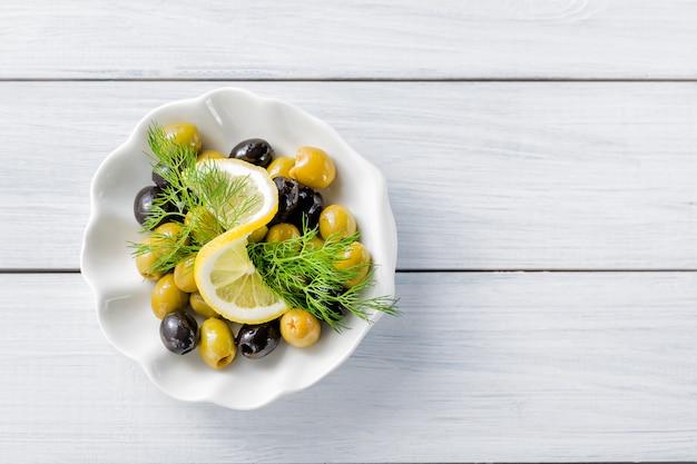 Fatias de limão com azeitonas e endro na mesa de madeira branca Foto Premium