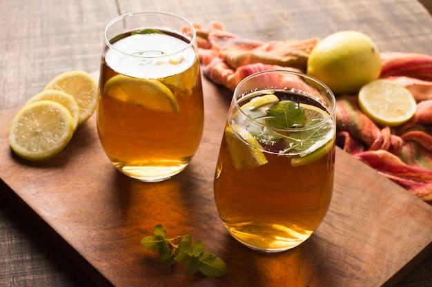 Fatias de limão gelado e folhas de hortelã chá de ervas na tábua de cortar Foto gratuita