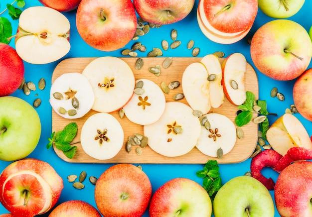 Fatias de maçã; sementes de abóbora e folhas de hortelã contra o fundo azul Foto gratuita