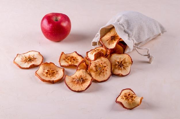 Fatias de maçãs de frutas secas em um saco ecológico e uma maçã vermelha madura repousam sobre uma superfície clara. Foto Premium