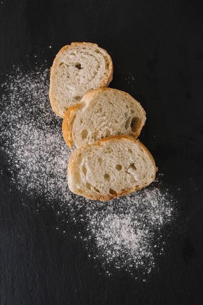 Fatias de pães frescos e farinha no fundo preto Foto gratuita