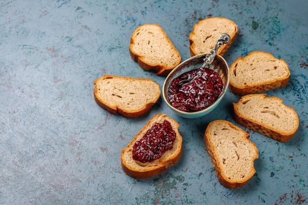 Fatias de pão com geléia de framboesa, lanche saudável fácil, vista superior Foto Premium