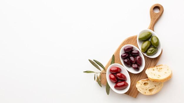 Fatias de pão e azeitonas verdes vermelhas roxas com espaço de cópia Foto gratuita