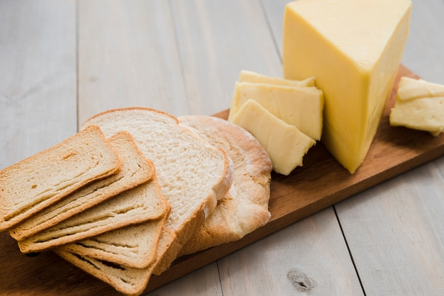 Fatias de pão e fatias de queijo na tábua sobre a mesa Foto gratuita