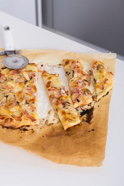 Fatias de pizza caseira em papel pergaminho Foto gratuita