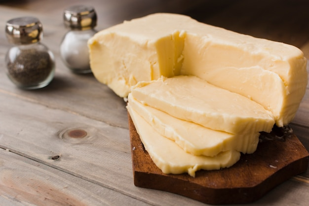 Fatias de queijo cheddar na tábua de cortar com shaker e pimenta na mesa Foto gratuita