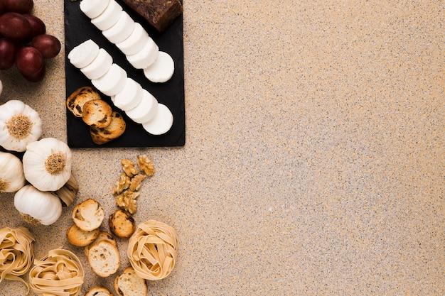Fatias de queijo de cabra e pão na pedra ardósia preta com alimentos crus sobre mármore texturizado Foto gratuita