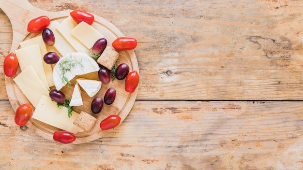 Fatias de queijo e blocos servidos com uvas e tomate cereja na tábua sobre a mesa Foto gratuita