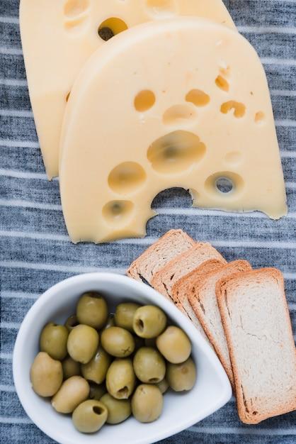Fatias de queijo emmental; pão e azeitonas frescas na toalha de mesa Foto gratuita